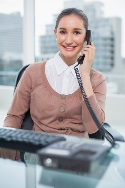 Smiling businesswoman picking up the phone