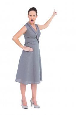 Angry gorgeous woman in classy dress pointing finger up