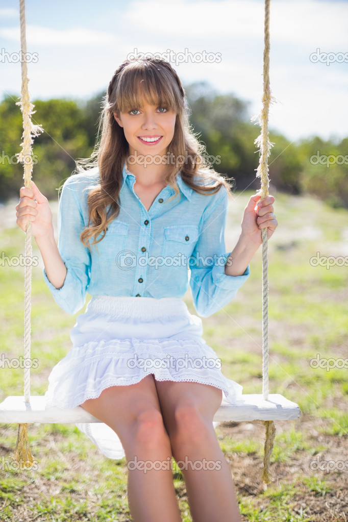 Cheerful young model posing while sitting on swing