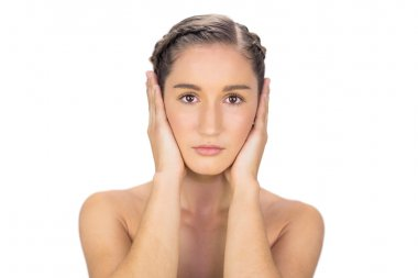 Unsmiling woman hands on ears