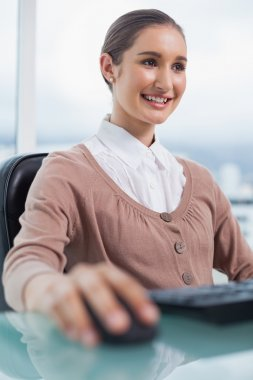 Happy gorgeous businesswoman working on her computer