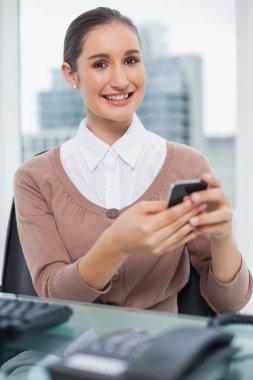 Cheerful beautiful businesswoman text messaging