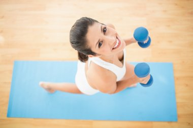 Happy woman exercising with dumbbells on blue exercise mat