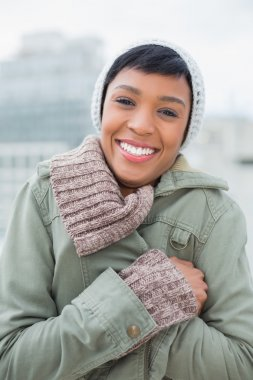 Delighted young model in winter clothes closing her jacket