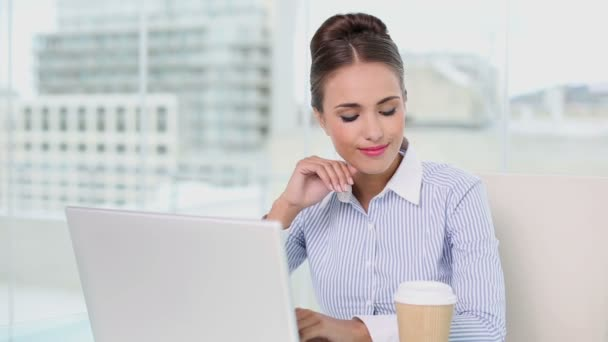 Young businesswoman working on her laptop drinking coffee