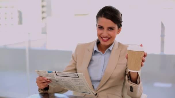 Nyugodt, szép üzletasszony újság olvasása közben kávét iszik