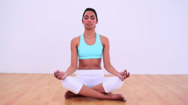 Calm woman meditating in lotus position