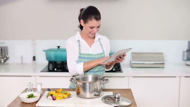 schöne Brünette nach einem Rezept auf ihrem Tablet-PC, während sie Abendessen zubereitet