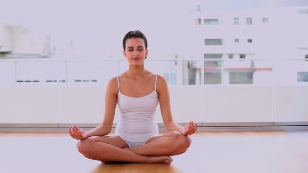 Calm beautiful woman relaxing in yoga position