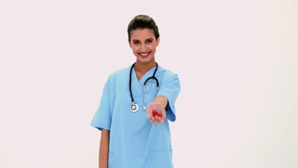 obsah krásná sestra ukazuje červené prášky v ruce