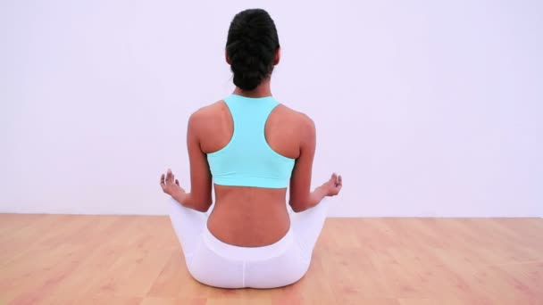 Fit woman meditating in lotus position
