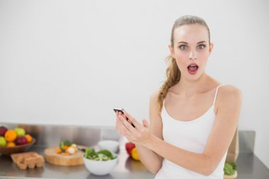Shocked young woman holding smartphone