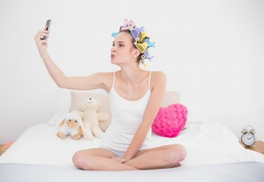 Woman in hair curlers taking a picture of herself with mobile phone