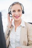 Fotografie Smiling blonde call centre agent interacting with customer
