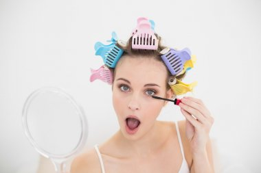 Woman in hair curlers opening her mouth while applying mascara