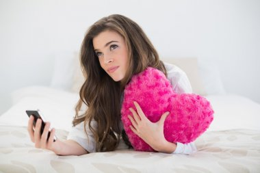 Woman holding a mobile phone and a heart-shaped pillow