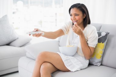 Pleased young woman in white clothes eating popcorn while watching tv