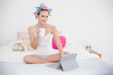 Stern woman in hair curlers holding a cup of coffee