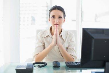 Troubled stylish brunette businesswoman praying