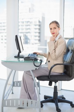 Thoughful blonde businesswoman posing in bright office stock vector