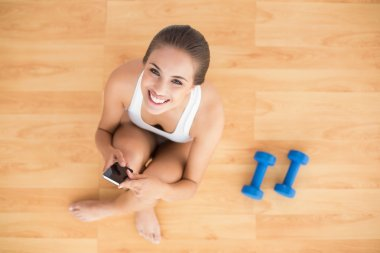 Smiling sporty brunette holding a mobile phone