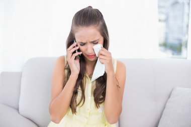 Crying young brunette holding mobile phone and tissue