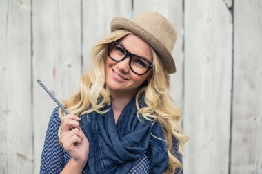Smiling trendy blonde holding pencil