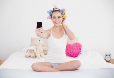 Smiling woman in hair curlers taking a picture of herself with mobile phone