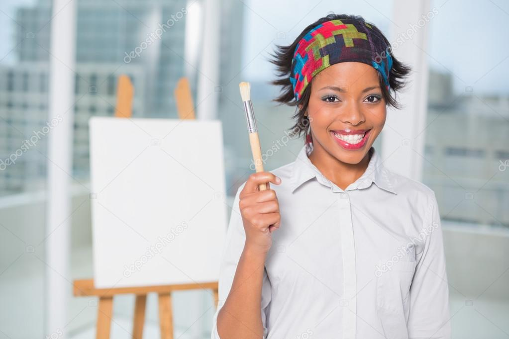 Smiling artist showing her brush while looking at camera