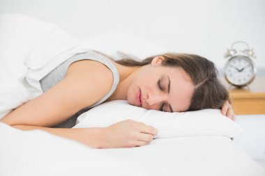 Cute sleeping woman lying in her bed under the cover