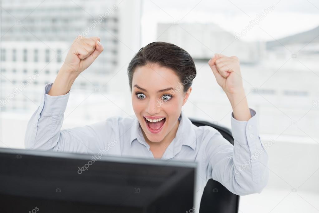 Femme daffaires excité se penche sur lécran dordinateur de bureau