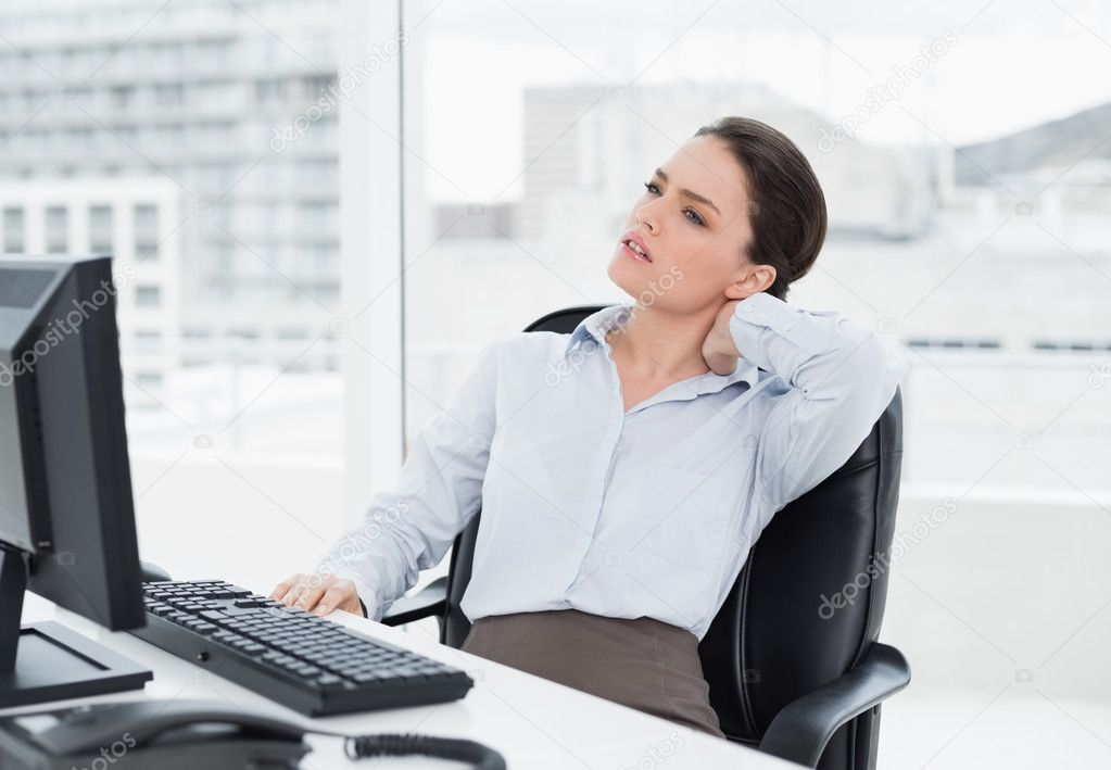 Businesswoman With Neck Pain Sitting At Desk Stock Photo