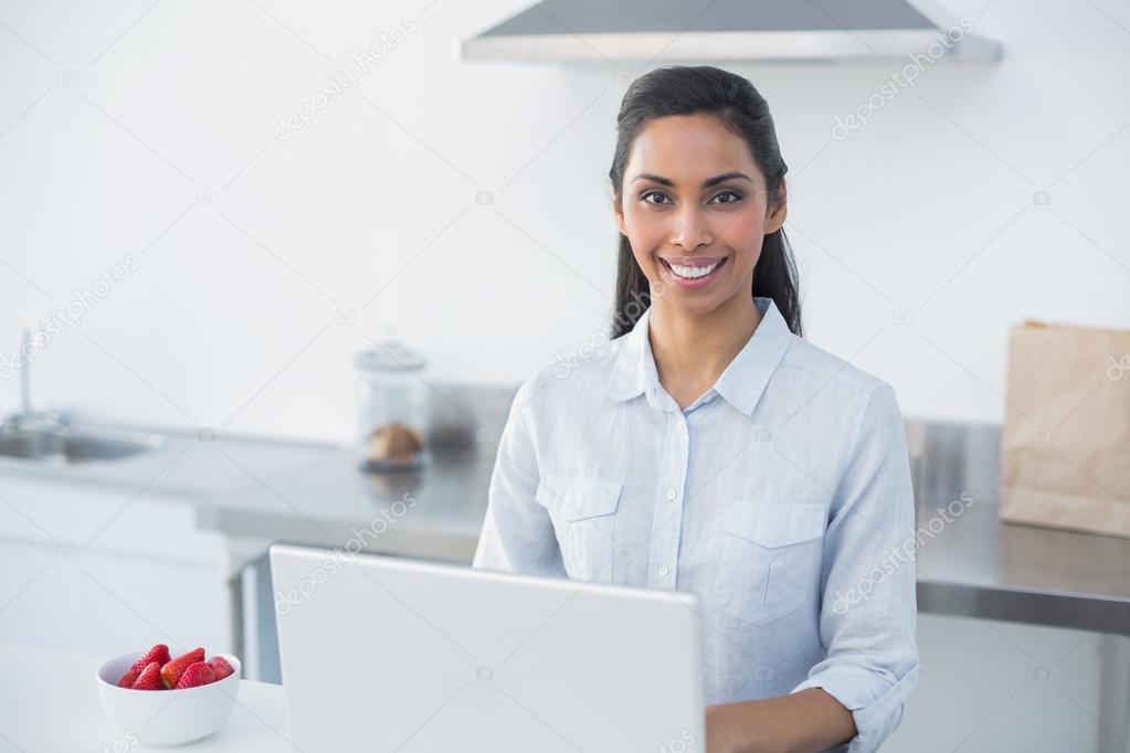 Inhalt der Frau mit ihrem Notebook stehen in hellen Küche ...
