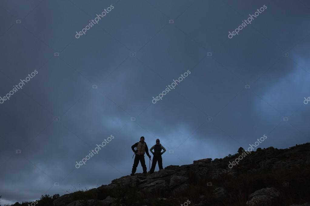 Couple with hands on hips on rocky landscape against sky at nigh