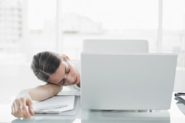 Pretty exhausted businesswoman sitting at her desk sleeping