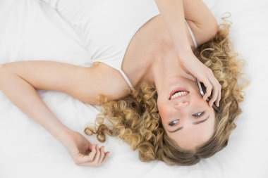 Pretty laughing blonde lying on bed phoning with mobile phone