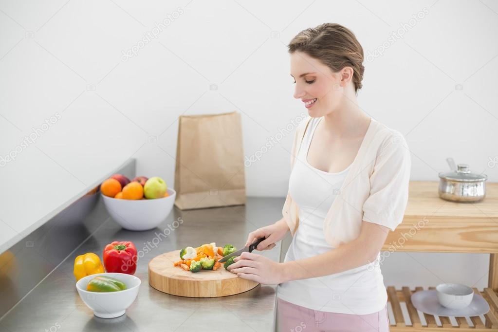 Fröhliche junge Frau schneiden Gemüse stehen in ihrer Küche ...