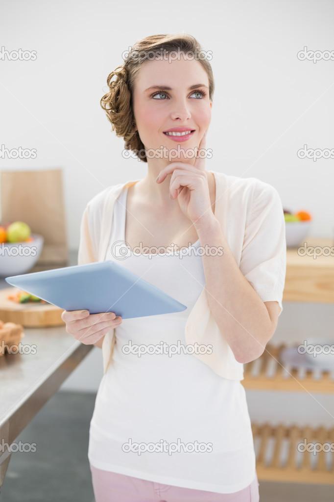 lächelnd denken halten ihr Tablet stehen in Küche — Stockfoto ...