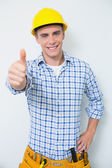 Photo Portrait of a handyman in yellow hard hat gesturing thumbs up