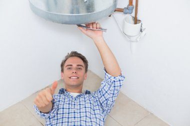 Technician gesturing thumbs up under hot water heater