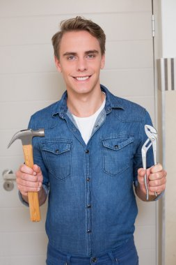 Smiling handyman holding wrench and hammer