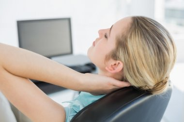 Chic businesswoman relaxing sitting on her swivel chair