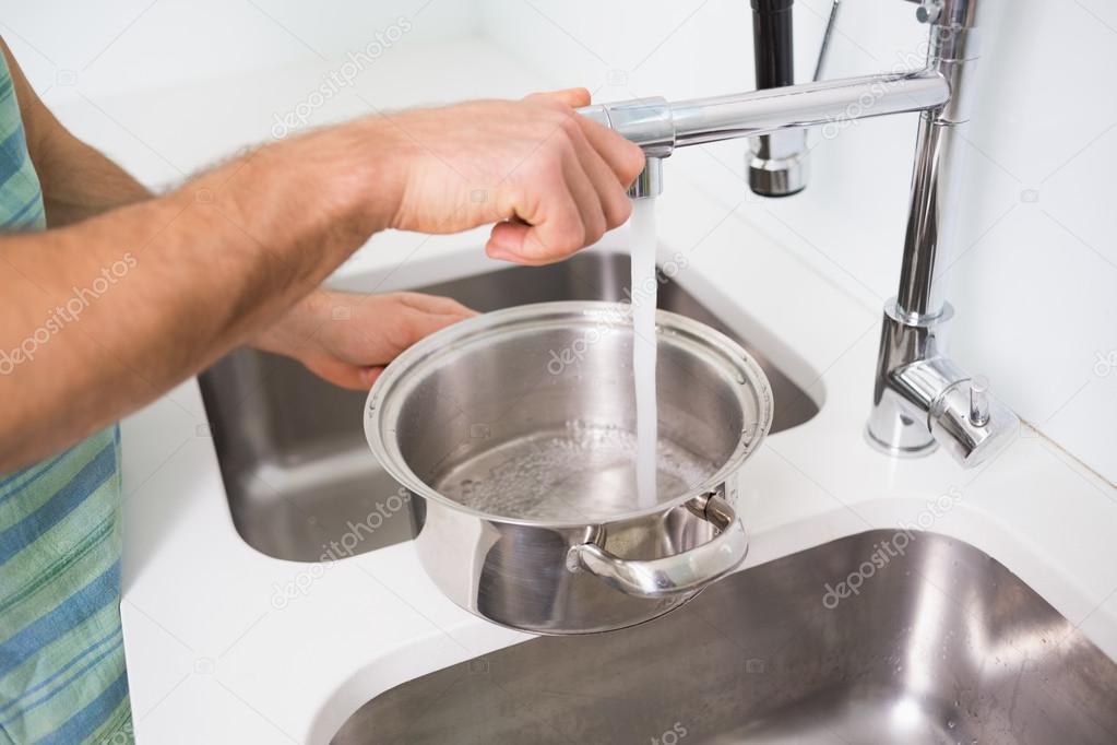 Hand, die Pfanne mit Wasser bei Küchenspüle zu füllen — Stockfoto ...
