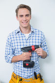 Photo Portrait of a smiling handsome young handyman holding drill