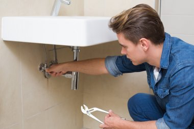 Young plumber with wrench by sink in bathroom