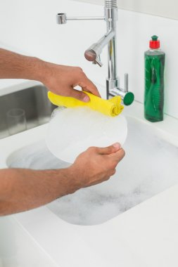 Mid section of man doing the dishes at kitchen sink