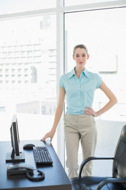 Calm businesswoman standing thoughtful in her office