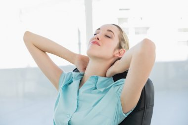 Beautiful peaceful businesswoman relaxing on her swivel chair