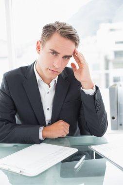 Businessman suffering from headache at office desk