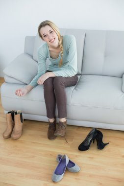 Gorgeous smiling woman tying her shoelaces sitting on couch
